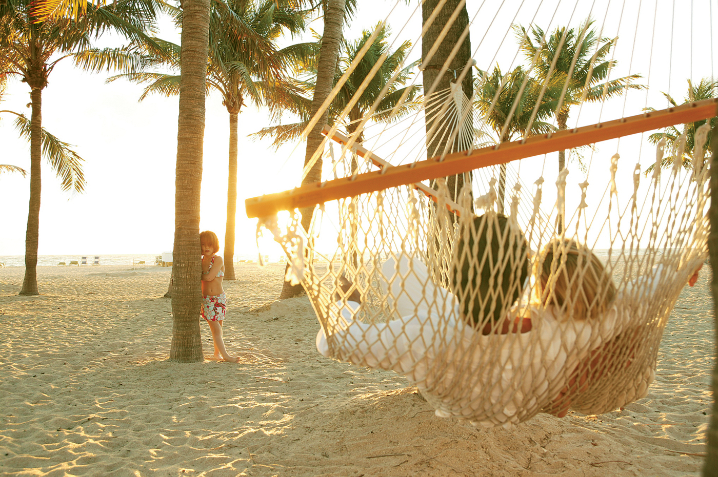 Parents in hammock with child nearby